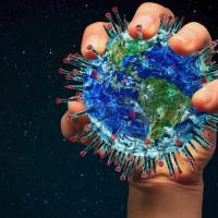eine Hand hält die Weltkugel, dargestellt als Coronavirus