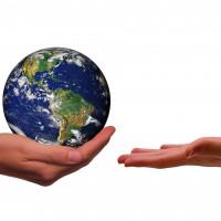 Erde wird von einer Hand gehalten, eine zweite Hand will sie in empfang nehmen